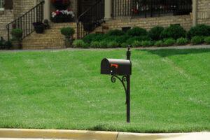 black metal mailbox on green lawn